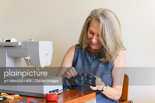 Older woman smiling while stitching handmade cloth masks at home - p1166m2201405 by Cavan Images