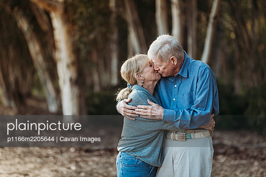 Portrait of senior adult retired couple kissing in forest - p1166m2205644 by Cavan Images
