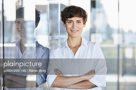 Portrait of smiling businesswoman in office - p300m2081148 by Rainer Berg