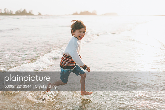 Cheerful boy running in water at beach - p300m2213944 by Crystal Sing
