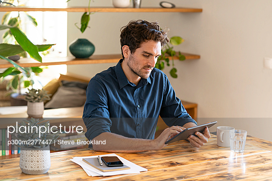 Pensive male freelancer using digital tablet while sitting at table in home office - p300m2277447 by Steve Brookland