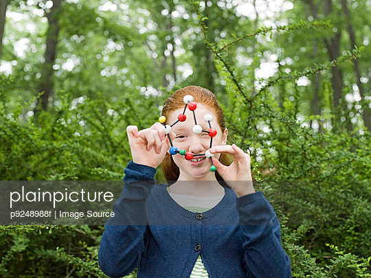 A girl holding a dna model - p9248988f by Image Source