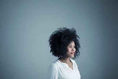 Portrait smiling mixed race young woman with curly black afro hair looking away - p1192m1213278 by Hero Images