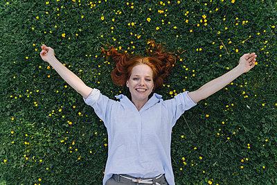Portrait of happy redheaded woman lying on a flower meadow - p300m2140836 by Kniel Synnatzschke
