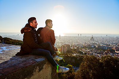 Boyfriends looking at cityscape while sitting on observation point during sunrise, Bunkers del Carmel, Barcelona, Spain - p300m2256686 by Veam