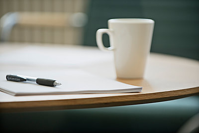 Notepad and pen on table, Stockholm, Sweden - p312m894857f by Johner