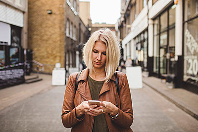 Young woman using mobile phone on road in city - p426m1442711 by Maskot