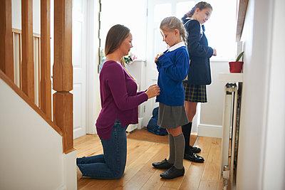 Woman fastening daughter's school cardigan in hallway - p429m1504606 by Peter Muller