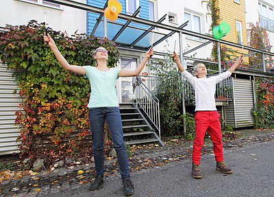 Brother and sister playing with spinning tops outside house - p429m875744f by Sigrid Gombert