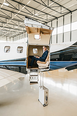 Businessman sitting in private jet - p586m1208551 by Kniel Synnatzschke