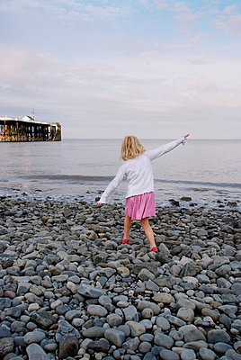 Rearview of blonde girl walking on stony beach with arms raised - p5970229 by Tim Robinson