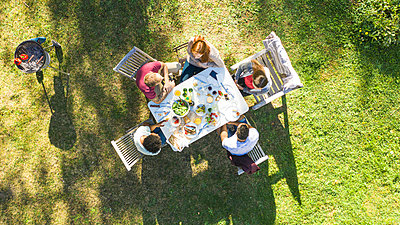 Happy young friends eating around a table in garden - p623m2294751 by Gabriel Sanchez