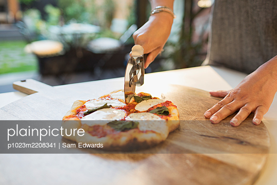 Woman cutting fresh homemade pizza with slicer - p1023m2208341 by Sam Edwards