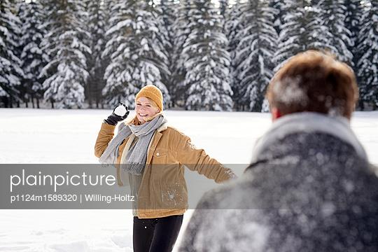 Junges Paar macht eine Schneeballschlacht - p1124m1589320 von Willing-Holtz
