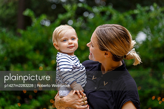 Mother holding baby girl, outdoors, smiling - p1427m2283228 by Roberto Westbrook