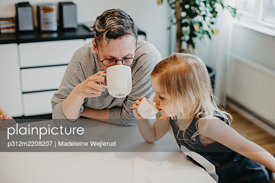 Mother and daughter drinking at table - p312m2208207 by Madeleine Wejlerud