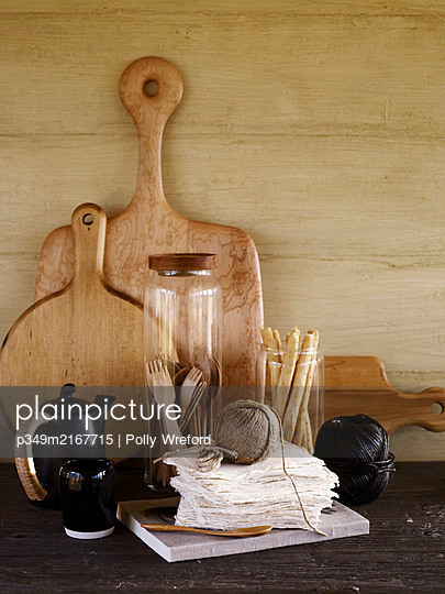 Ball of string with black ceramic teapot and wooden chopping boards - p349m2167715 by Polly Wreford