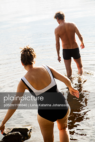 Sweden, Dalarna, Runn, Falun, Mature woman and man wading in lake - p352m1186940 by Lena Katarina Johansson