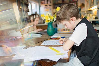 Boy doing homework at dining table - p1023m2200998 by Paul Bradbury