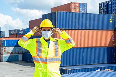 Container worker wearing protection face mask during coronavirus - p1166m2236876 by Cavan Images