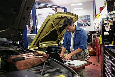 Mechanic diagnostic testing at laptop auto repair shop - p1192m1063901f by Hero Images