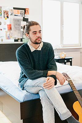 Alternativer, junger Mann auf Bett mit Gitarre, Portrait - p1358m1215568 von Nolting