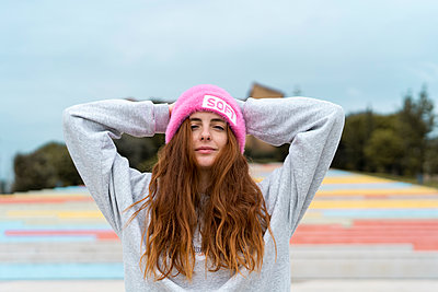Portrait of smiling redheaded woman wearing pink cap with the word 'soft' - p300m2079051 von VITTA GALLERY