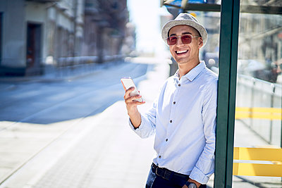 Happy young man with cell phone at a tram stop in the city - p300m2102577 by Bartek Szewczyk