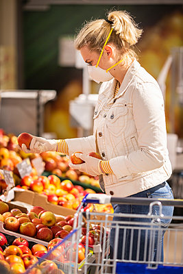 Teenage girl wearing protectice mask and gloves choosing apples at supermarket - p300m2225038 by Anke Scheibe