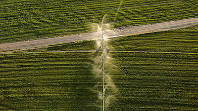 Aerial view of agricultural sprinkler spraying field - p300m2264401 by Aitor Carrera Porté