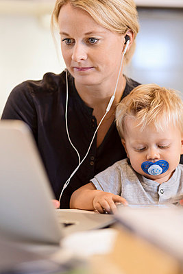 Mother with baby boy listening music on laptop at home - p426m1017819f by Maskot