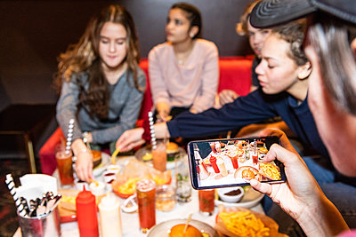 Cropped image of teenage boy sitting with friends while photographing food and drinks on table at restaurant - p426m1588375 by Maskot