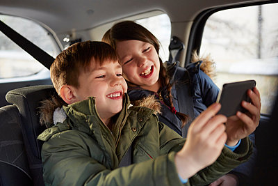 Boy and sister taking laughing selfie in car backseat - p429m1407916 by Emma Kim