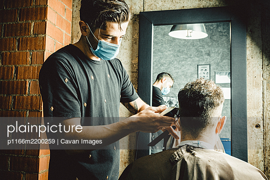 beautician and hairdresser working with mask for the covid19 virus - p1166m2200259 by Cavan Images