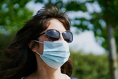 Woman in mask in park - p1166m2201416 by Cavan Images