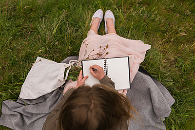 Young woman sitting on a meadow writing down something in her notebook - p300m1157321 by Boy photography