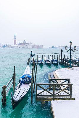 Gondolas with snow at St Mark's waterfront, Venice, Veneto, Italy. - p651m2034009 by Marco Bottigelli