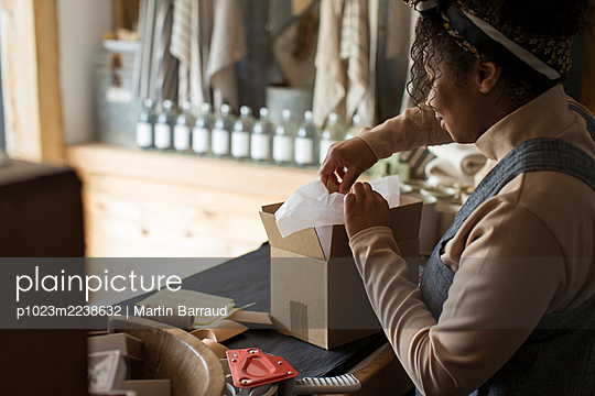 Female shop owner preparing package at shop counter - p1023m2238632 by Martin Barraud