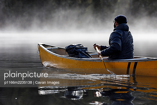 Bearded man paddles boat in lake during foggy weather - p1166m2235138 by Cavan Images