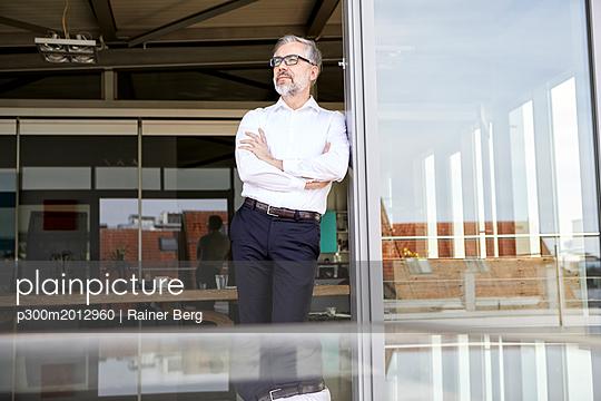 Businessman standing at French door thinking - p300m2012960 von Rainer Berg
