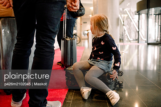 Girl sitting on suitcase with family standing at reception in hotel - p426m2102045 by Maskot