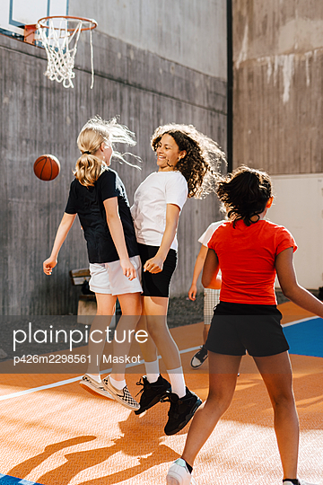 Female friends celebrating after goal at basketball court - p426m2298561 by Maskot