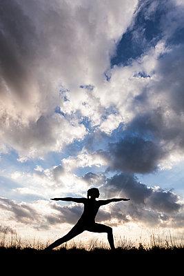 Frau beim Yoga-Training als Silhouette vor bewölktem Himmel - p105m1181536 von André Schuster