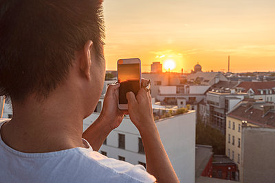 Young man with smartphone takes a picture of the sunset, Berlin - p1332m2204577 by Tamboly
