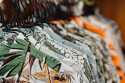 Close-up of shirts hanging on rack at clothing store - p300m2131664 by VITTA GALLERY