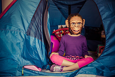 Mixed race girl wearing mask in tent - p555m1419549 by Inti St Clair