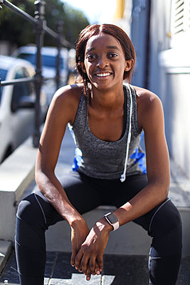 Young female runner sitting on city sidewalk, portrait - p924m2090577 by Bean Creative