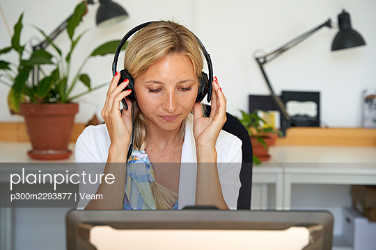 Female customer service representative wearing headphones at office - p300m2293877 by Veam