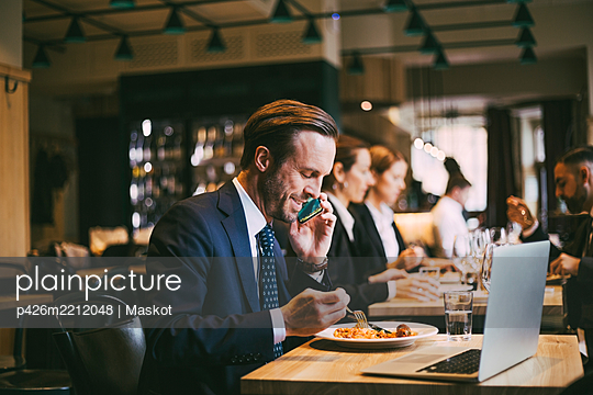 Smiling male business person talking on phone while eating food in restaurant - p426m2212048 by Maskot
