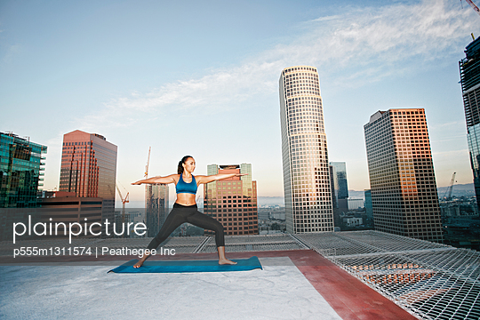 Mixed race woman practicing yoga on urban rooftop - p555m1311574 by Peathegee Inc